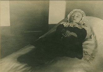 Little girl laid out on a bed