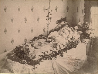 Baby in a casket surrounded by flowers