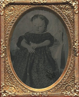 Baby girl holding a small doll